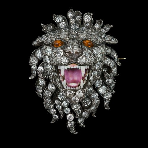 A striking and realistically modeled brooch of a roaring lion decorated throughout with old European-cut diamonds, set with bright oval cabochon citrine eyes and finely enameled teeth and tongue, mounted in silver and gold, probably English, c.1860.