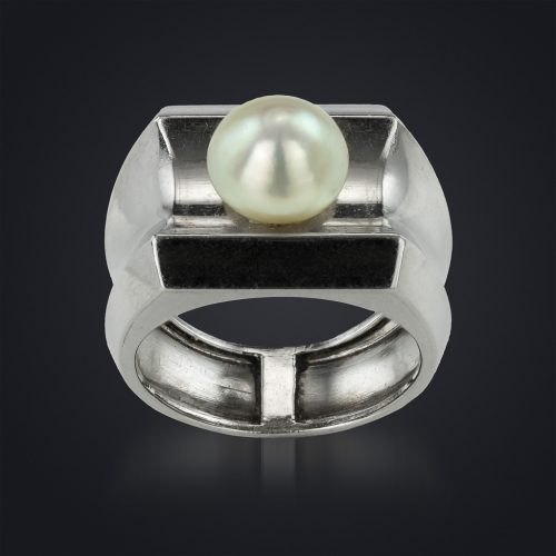 A bold and impressive wide platinum ring, the concave centre set with a fine natural pearl, René Boivin, Paris, 1937. Design by Juliette Moutard and accompanied by a certificate of authenticity from Françoise Cailles.