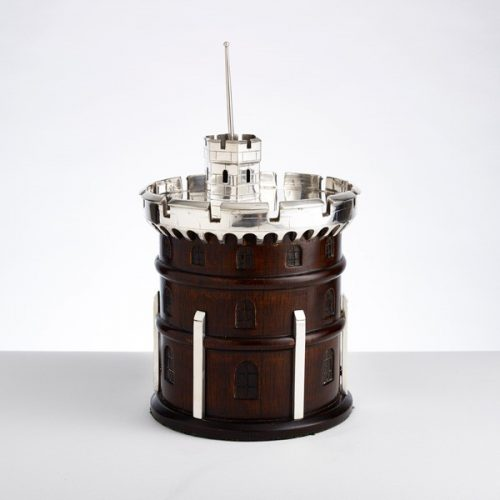 A great novelty ice bucket in the form of a tower. The base is mahogany & the turret is in fine quality silver plate. The interior has a porcelain liner circa 1920. 12