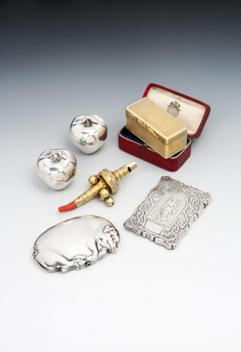 "A pair of Apples, one a Trinket Box and the other a scent Bottle; a Silver-gilt engine turned Snuff Box in original case; Silver-gilt and coral Rattle; Card Case engraved with ""Blind Justice""."