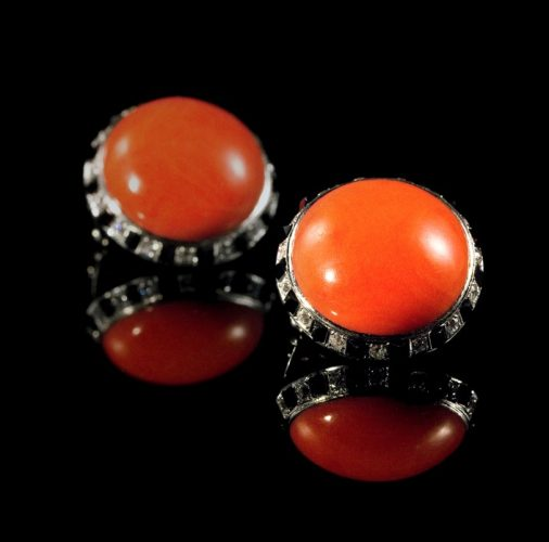 A pair of coral, black onyx and diamond set earrings. Mounted in platinum. Circa 1950s.