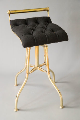 Harp stool with brass base and swivel seat re-upholstered in black and buttoned with brass studs.
