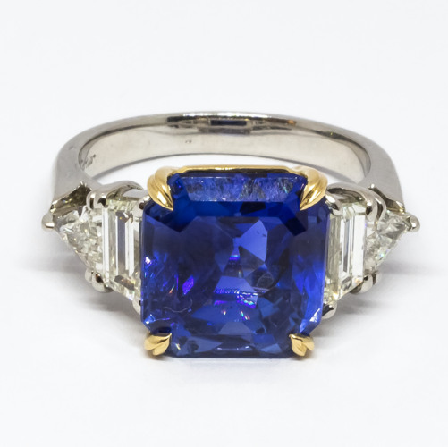 A Cartier sapphire ring, set with a 7.51ct emerald-cut, non heat treated Burma sapphire. The shoulders are set with a trapezoid and a trilliant-cut diamond on each side, weighing an estimated 1.60ct, mounted in platinum, with an 18ct yellow gold claw setting for the sapphire. Signed Cartier, numbered 802647, in its original Cartier box. Accompanied by a GIA certificate.