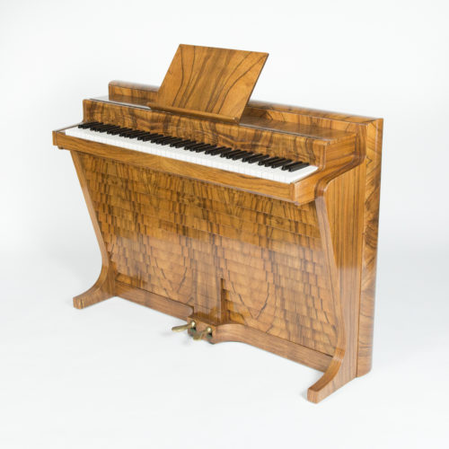 An Andreas Christensen walnut piano, designed by Poul Henningsen, Danish, 1939.