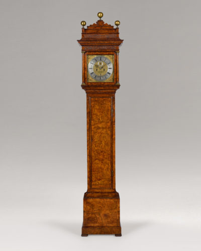 An exceptional Queen Anne period burr walnut longcase clock with square dial and caddy top by this famous maker. The case is veneered with figured walnut of excellent colour and patination. The pull-forward caddy top hood is flanked by turned, walnut veneered pillars with brass capitals. The original caddy top is surmounted by two gilt ball finials and a third which is mounted on a central block. The 12 inch square dial has an applied chapter ring with winged cherubs and foliate spandrels. The centre is finely matted with an applied seconds ring and an aperture to view the day of the month above VI. The blued steel pointers are finely pierced and the maker's signature – Christopher Gould, London - is engraved on an oval reserve within the matted dial centre. The five pillar movement has rack striking with the hours sounded on a bell. As one would expect from a maker of Gould's stature, the movement is excellent quality with chamfered cocks and thick plates. Date: circa 1710 Height: 100 in (254 cm) Width: 19 ½ in (49.5 cm) Depth: 10 ¼ in (26 cm) * Christopher Gould was made a Free Brother in The Clockmakers' Company in April 1682. He was later appointed Beadle in 1713. He died in 1718 and examples of his work can be seen in many public collections including the British Museum. He was one of the finest makers of the period and his cases are on a par with those of Thomas Tompion and Daniel Quare. In fact, given the similarities, there is a strong probability that this case was made by the same cabinet maker as those of Tompion and Quare.