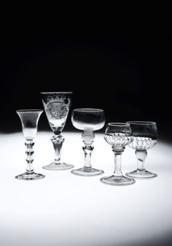 "Left to Right: A scarce English 4 knop Wine Glass, c.1760-70, excellent quality and colour. An extremely rare English Silesian stemmed ""Royalist"" Goblet, c.1715-1725; with panel molded stem bearing 6 four sided stars at the shoulder of the knop. The Royal coat of arms is engraved with strength and confidence and is typically English in its interpretation and execution. The Glass is beautifully proportioned and is engraved on the folded foot with a wreath of vine. A rare English Mead Coin Glass, c.1711, the cup shaped bowl over a hollow knop sided by annulations and holding a 1711 coin, above an inverted baluster with tear and basal knop on a folded foot. An English Mead Glass c.1720. Lovely inverted form to the bowl with strong gadrooned molding to the bottom of the bowl. Double ring shoulder knop on a long plain stem with basal knop and a generous folded foot. Beautiful colour and finish to the metal. A scarce English Mead Coin Glass c.1690-1700; this rare Mead Glass contains a Charles II groat in its stem. The generous bowl with gadrooned bottom all on an inverted baluster hollow stem on a folded foot. Provenance: The Meyer Collection, 2013. The Dr. Light Collection, 1970."