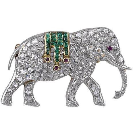 Platinum, Gold and Diamond Walking Elephant Brooch of instantly recognisable quality. The Platinum body pave set with Rose Diamonds and a Ruby eye and a howdah blanket of 17 square Emeralds and 3 circular Rubies. The reverse with a yellow Gold pin and catch and a Gold safety lock, the pin numbered 9609 and the French Eagles Head mark for 18k Gold and also marked on the catch. At this time, the French had not yet evolved a Platinum mark so precious metal was given an 18k mark. Condition: Good Weight: 6.6g Dimensions: 1 inch wide x 9/16 inch high French: circa 1910