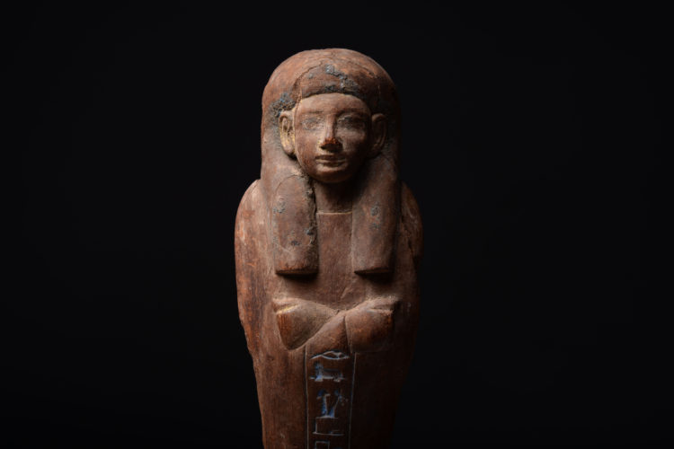 The only surviving shabti made for Iweferbaku. Finely carved, with remnants of blue and gold gesso. A single column of hieroglyphs, inlaid with Egyptian blue, reads,
