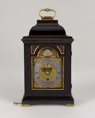 A good George II period ebonised pearwood bracket of small size, the 4 ¾ inch arched brass dial with inset datework below XII and a central dummy pendulum aperture. The 8-day timepiece movement has a restored verge escapement with pull hour and quarter repeatwork on 7 bells. Date: circa 1745 – 1750 Height: 13 ½ in (34.5 cm) excluding handle Width: 8 in (20.5 cm) Depth: 5 ½ in (14 cm) * John Ellicott was born in 1706 and established his business in Swithin's Alley, Royal Exchange in 1728. He was the inventor of a compensation pendulum and he developed the use of the cylinder escapement. Like his peer George Graham, he became a member of the Royal Society, for which he wrote several papers. He was appointed Clockmaker to the King and he designed the London Hospital clock. He died suddenly in 1772 and was succeeded by his son. His work can be found in museums and royal collections throughout the world.