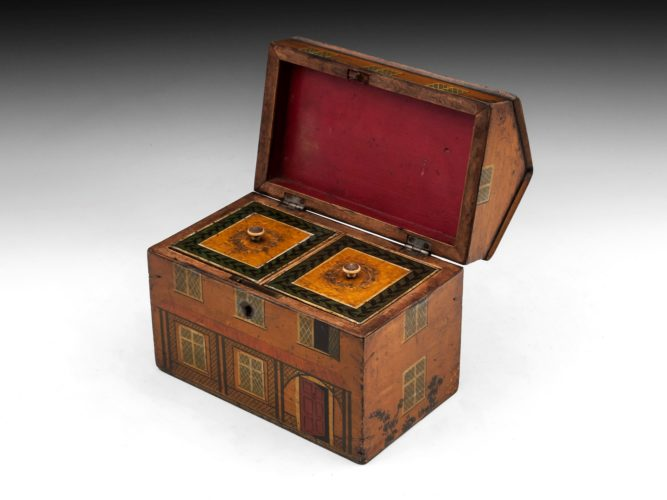 Rare Folk Art tea caddy in the form of a country cottage. The exterior of this delightful charming house tea caddy is adorned with painted windows, doors and surrounding plants. The interior of the cottage tea caddy features two lidded compartments with turned bone handles. This charming cottage tea caddy comes with a fully working lock and tasselled key. Circa 1800.