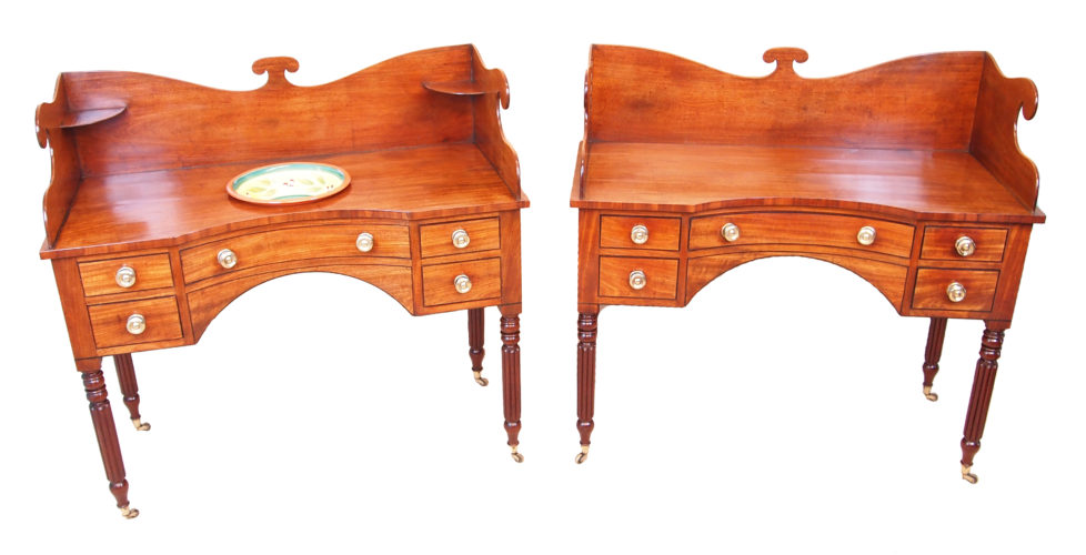 An Exceptional And Extremely Rare Pair Of Regency Period Mahogany Dressing Tables Having High Shaped Gallery Tops Above Concave Fronts And Drawers Fitted With Original Turned Brass Knobs Raised On Elegant Turned And Reeded Legs Terminating On Original Brass Castors