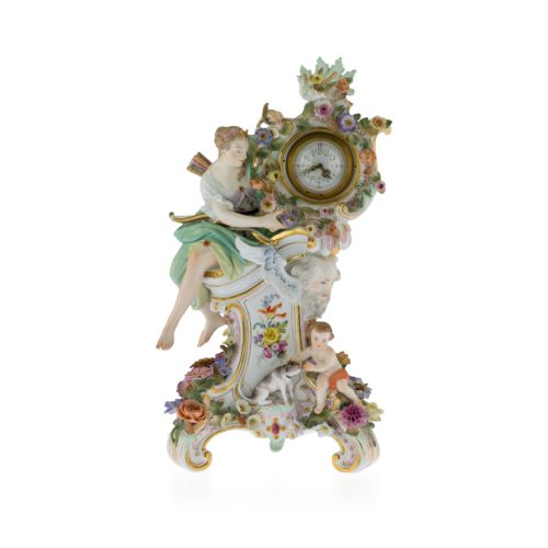 A Meissen Mythological flower-encrusted clock, circa 1880. The clock case supported by a figure of Diana the Huntress, seated on a rocaille plinth painted with a vignette and applied with a winged mask of Father Time and a putto petting Diana's hound, on four scroll feet, after the model by J.J.Kaendler, 39 cm high