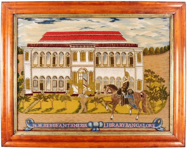 Rare 19th century wool work picture depicting a mounted Hussar outside the Sergeants Mess and Library at Bangalore, India. English. Circa 1870.