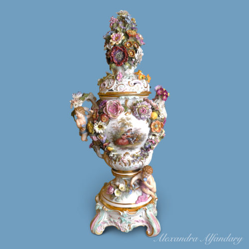 A large Meissen Potpourri Vase decorated with applied flowers and putti and romantic scene to front of vase