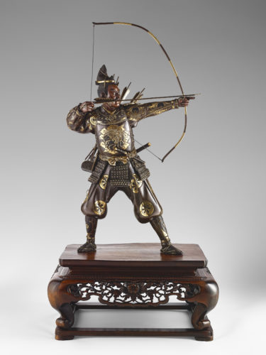 Japanese bronze Samurai Archer holding a bow in one hand and preparing to draw his arrow with the other, his robe has formal crests mon, with an aikuchi into his waist and a tachi suspended from the side, standing on a carved wood base, signed in a rectangular reserve Yoshimitsu 芳光, Meiji Period.