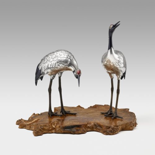 Japanese silvered bronze okimono pair of Manchurian cranes (tancho-zuru) with details in shakudo and gilt, on a wooden base, signed with chiselled characters on a gilt oval plaque Hidenao秀尚 (Shūshō), Meiji Period. In Japan the crane is an auspicious symbol of long life because of its fabled life span of a thousand years, luck and fidelity as cranes pair for life. Reference:
