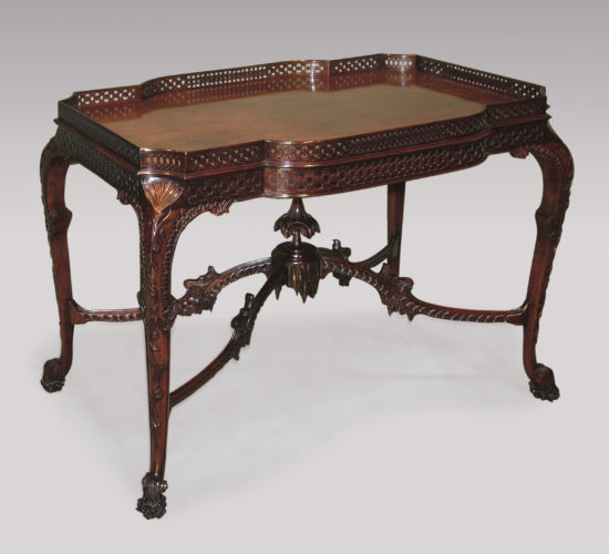 An important mid 19th Century Chippendale style mahogany Silver Table, having laminated pierced gallery to the shaped top, above blind fret frieze. The Table profusely carved with shells, flowers, gadrooning and icicles, supported on cabriole legs, joined by arched stretchers with central finial, ending on unusual carved scrolled feet. Circa 1860.