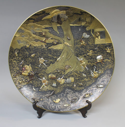 A Japanese iron inlaid multimetal plate decorated with a dramatic scene of a giant eagle stealing a catch from fishermen, signed Komai, c1880, 46cm diameter