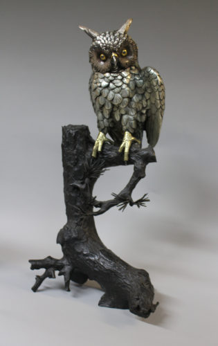 A Japanese silvered bronze long eared owl on a naturalistic bronze base, signed to underside, c1880, 55cm high