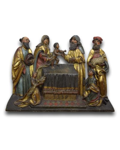 An imposing limewood retable group depicting the offering of Christ at the temple. The group comprises Joseph alongside the Virgin who is presenting the Christ child over the altar to the high priest, beside which is John the Baptist. The figures in the foreground, flanking the altar are most likely donor figures. Probably Alsace, dated 1559 & of the period. Measures 106 x 78cm.